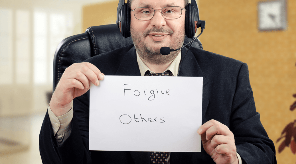 "Man holds sign that reads ""forgive others."""