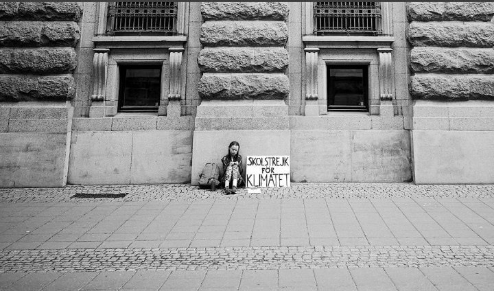 Greta Thunberg, aged 15, sits outside of Swedish Parliament in 2018 during the first solo school climate strike. A year later she's created a worldwide movement with millions.