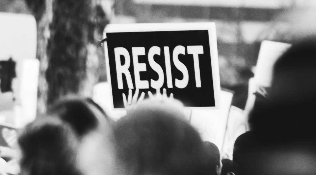 A picture of a sign that says Resist at a rally--introducing a piece about unhealthy and healthy law and order theologies