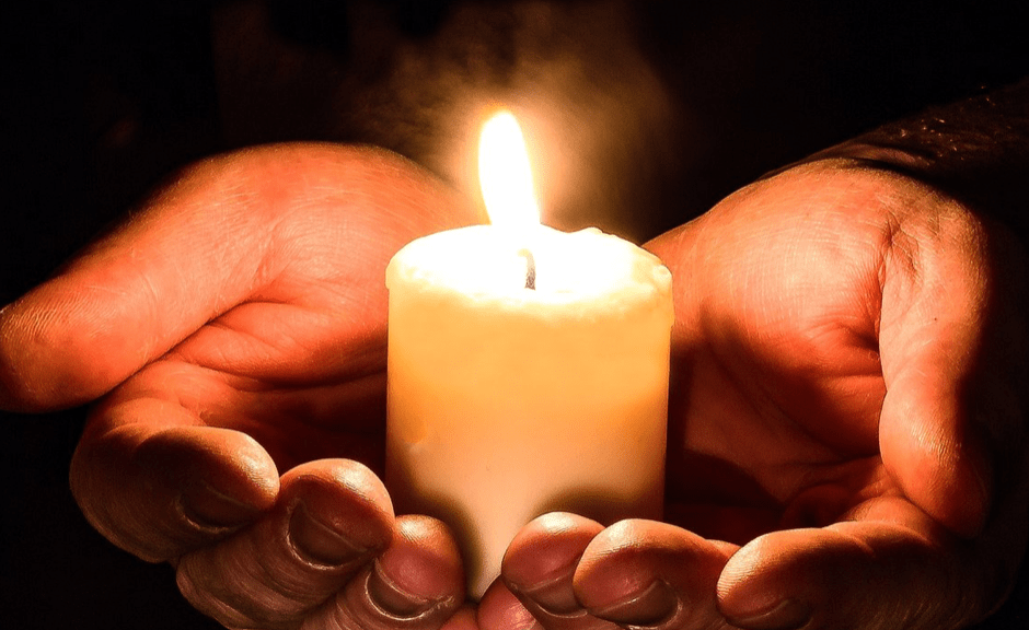 A lit candle in hands, introducing an article about non-toxic positivity