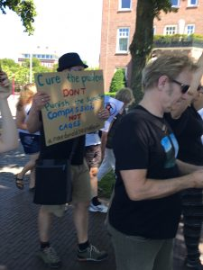 """Man holding sign that says: """"Cure the problem don't punish the symptom; Compassion not Cages."""""""