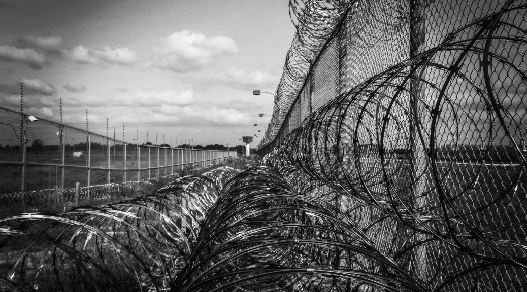 rhetoric and policies too often silence the voices of justice--this image highlights that with an image of a barbed-wire fence